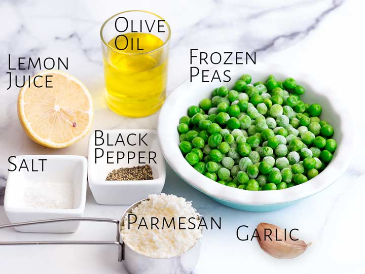 7 ingredients for pea pesto on a marble table