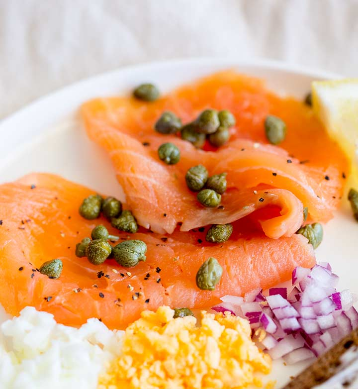 close up on two slices of smoked salmon scattered with capers on a white plate