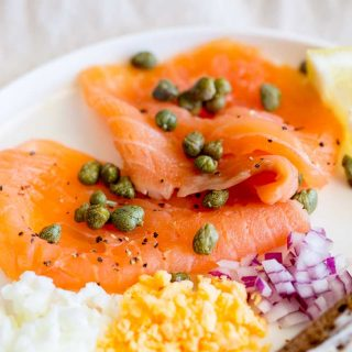 smoked salmon, capers chopped egg and red onion on a white plate