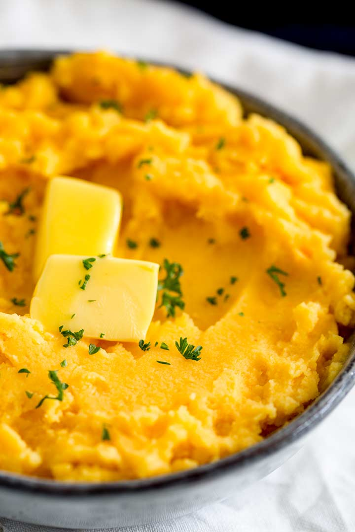 overhead view of yellow/orange sweet potato mash with two slices of butter on top