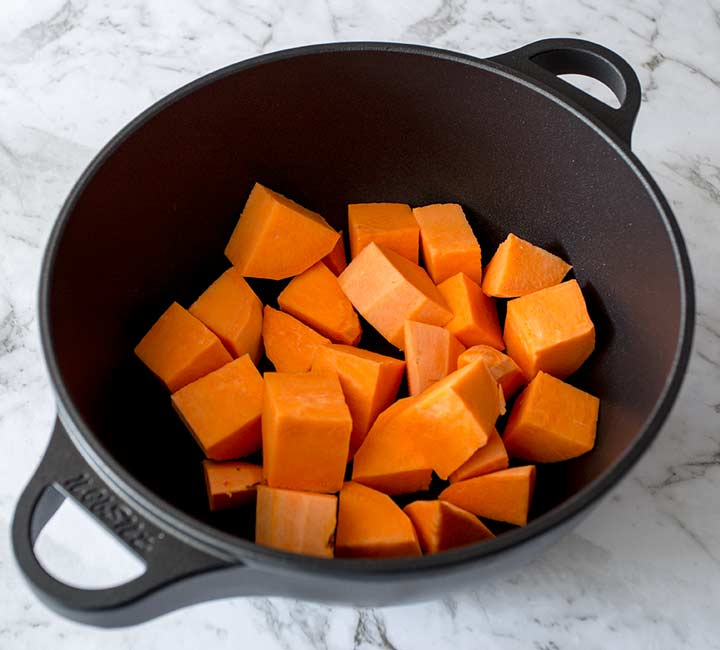 chunks of sweet potato in a black cast iron pan on a marble table