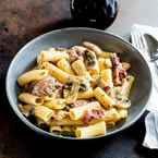 tube pasta with a creamy steak sauce in a grey bowl