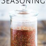 jar of creole seasoning on a wooden table with text at the top