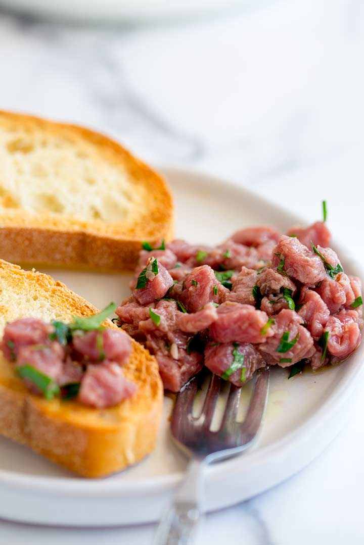 Carne Cruda being piled onto a slice of toasted bread