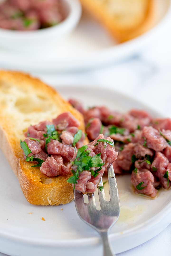 close up on the fork putting carne cruda onto a slice of toast