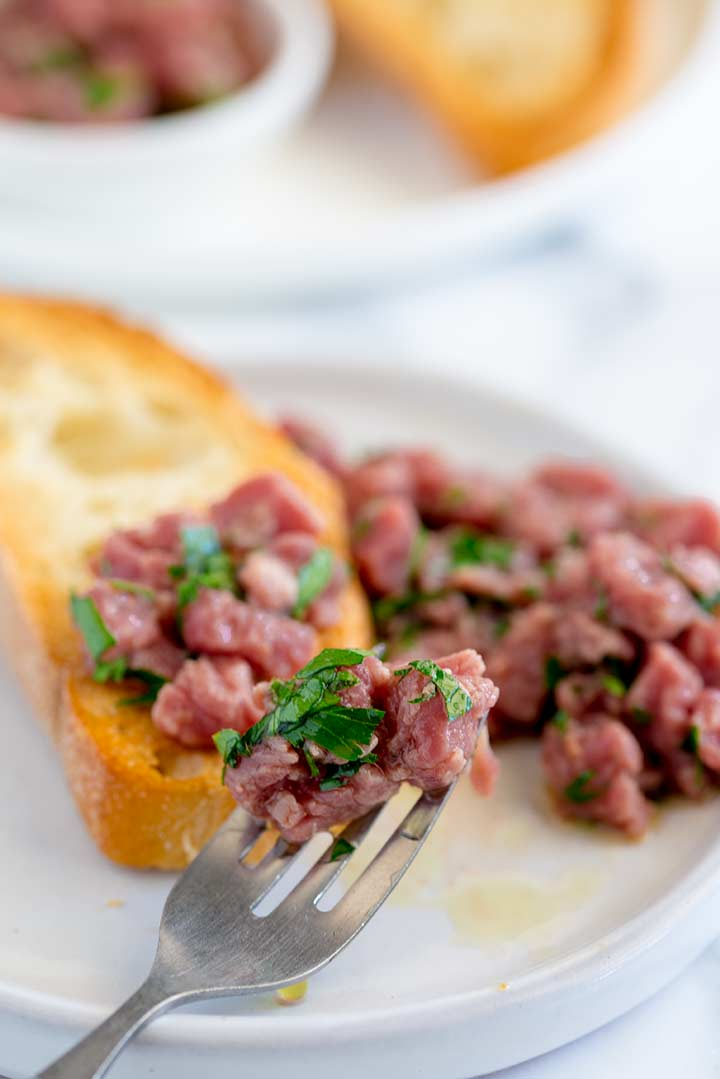 a silver fork picking up a pile of carne cruda and parsley