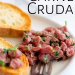 a white plate of carne cruda with text at the top