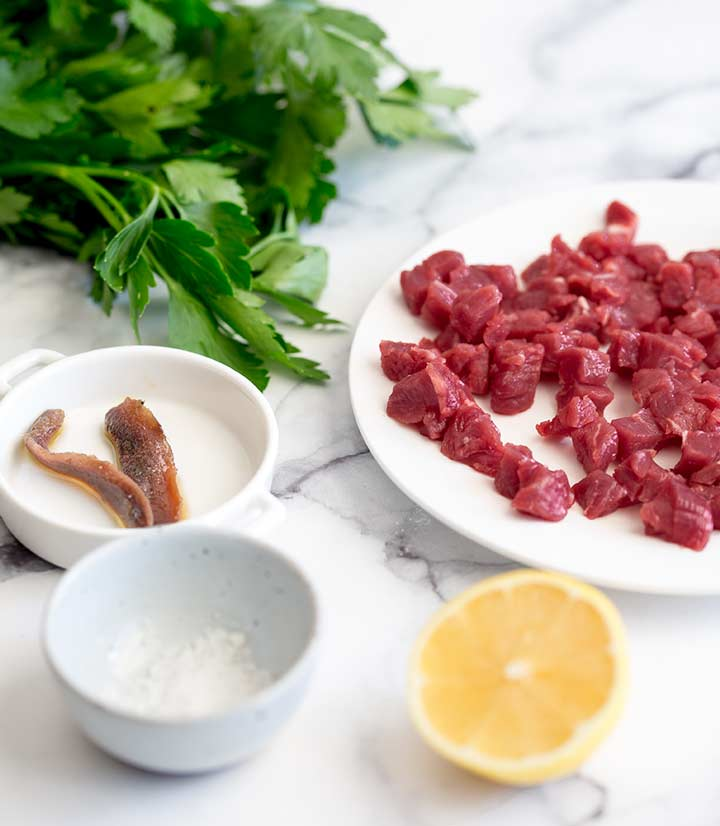 the ingredients for Italian Steak Tartare layer out on a marble worktop
