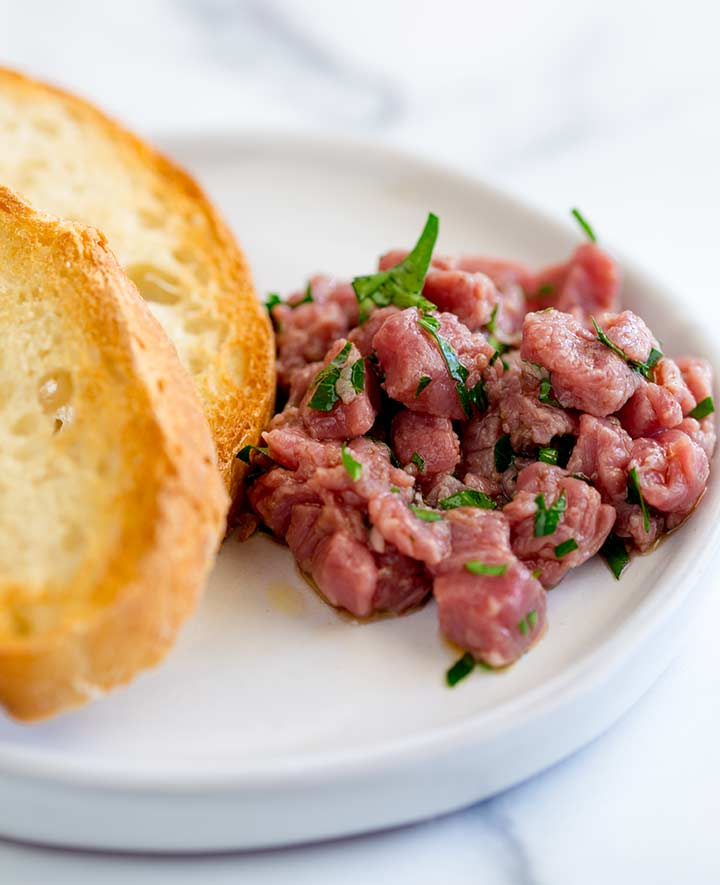 a small white plate with a pile of carne cruda sprinkled with parsley