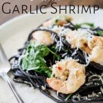squid ink pasta and shrimp on a white plate with text at the top