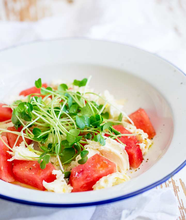 a white and blue plate of watermelon salad on a wooden table