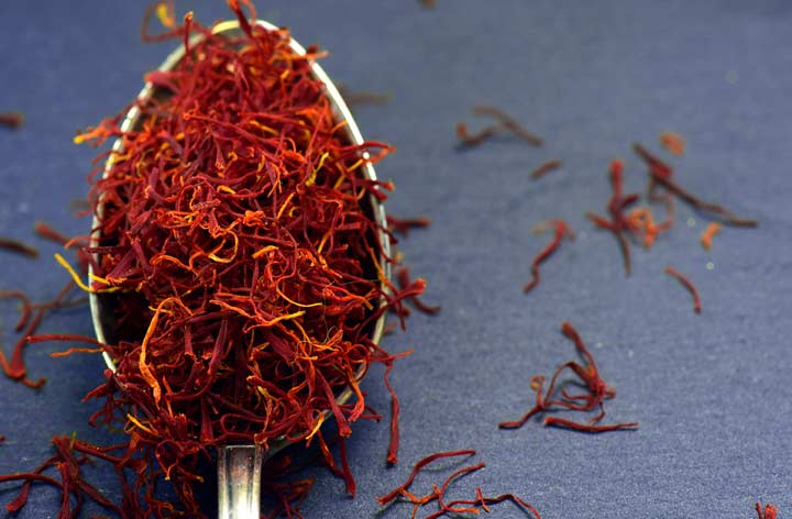 a silver spoon of saffron threads on a purple/blue background