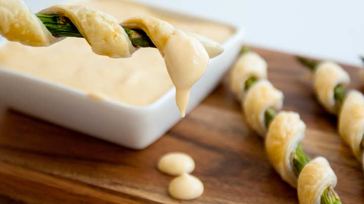 an asparagus wrapped in puff pastry dripping hollandaise sauce on a board