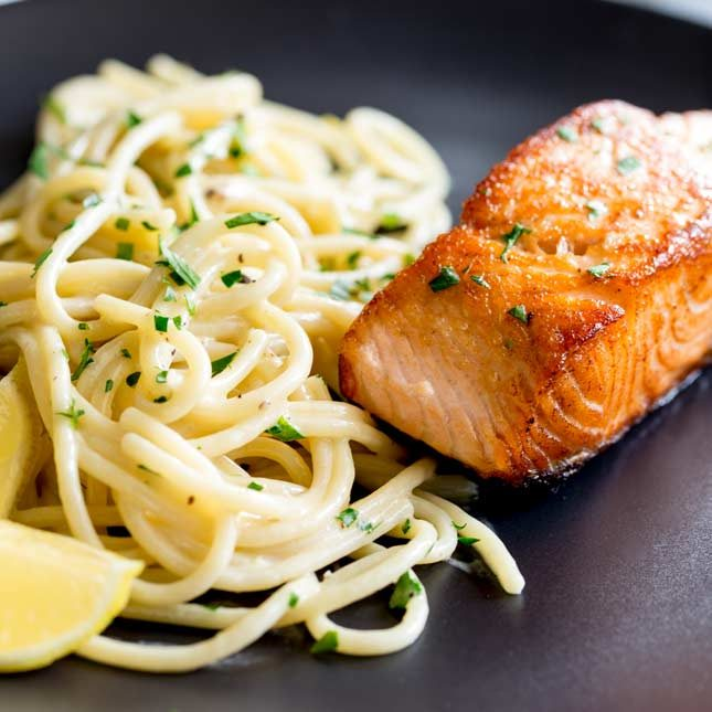 close up on the crispy salmon and pasta on a black plate