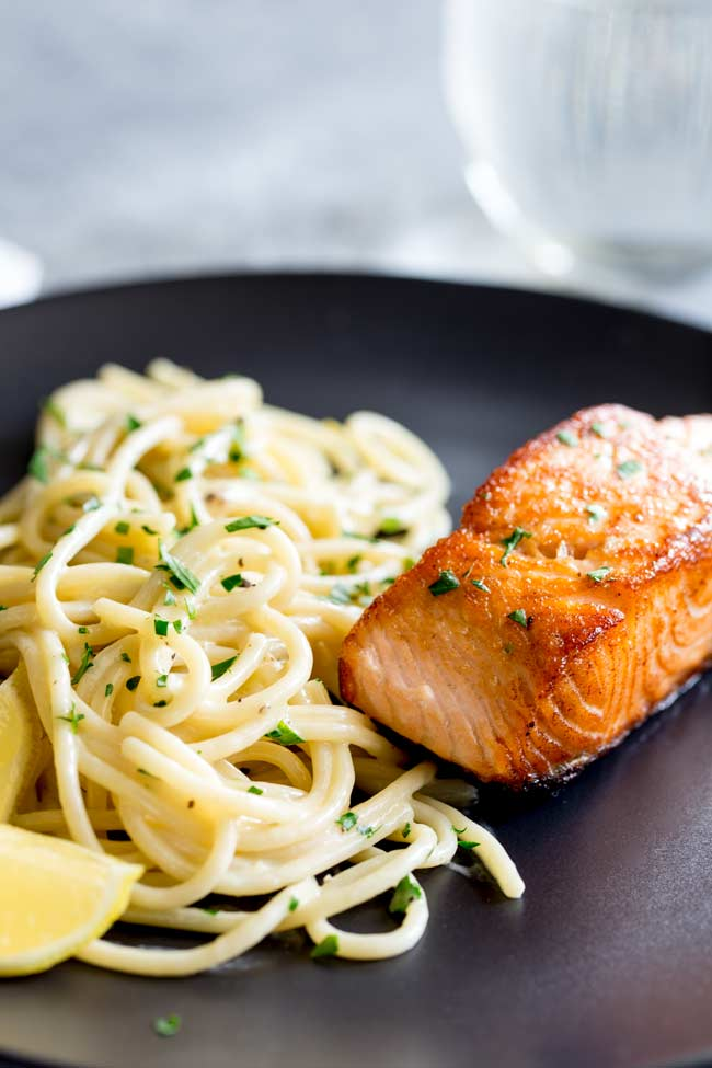 creamy spaghetti on a black plate with a seared salmon fillet
