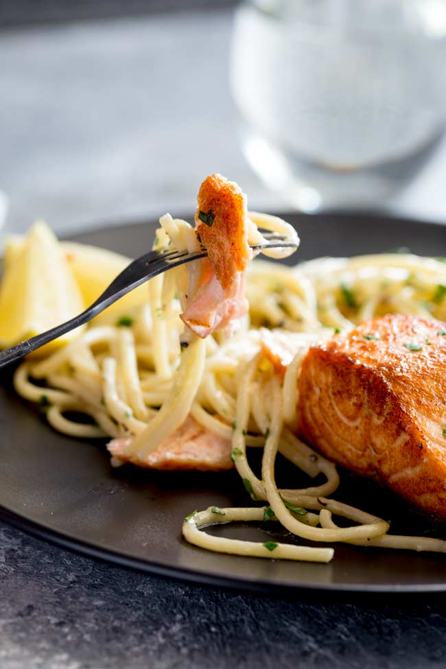 a silver fork lifting a piece of salmon and pasta up from a black plate
