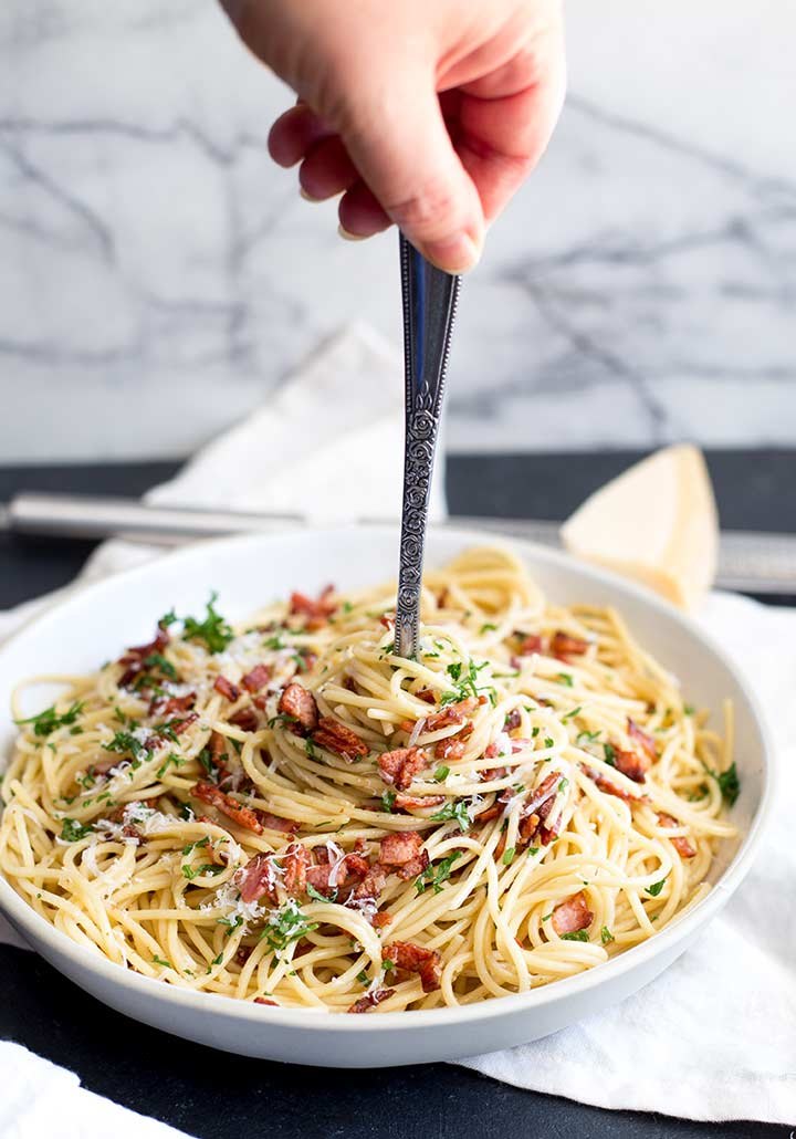 a hand holding a fork of swirled bacon pasta