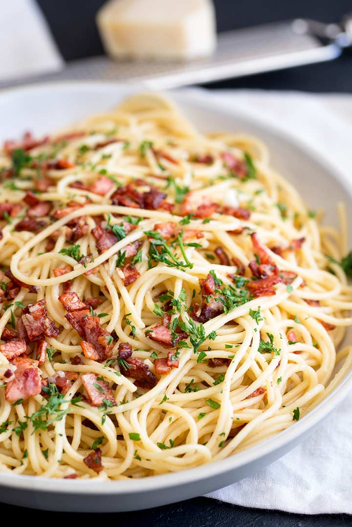 close up on a bowl of spaghetti with bacon and parsley on top