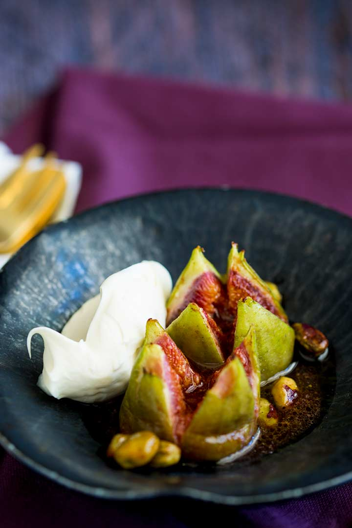 two figs in a black bowl with a quenelle of cream fresh on the side.