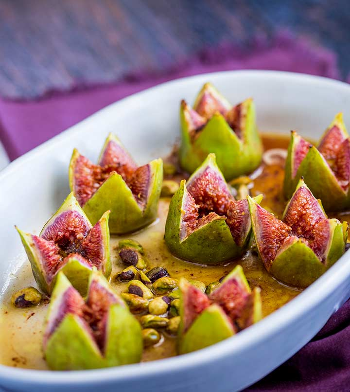 8 cooked figs in a oval white baking dish on a purple table