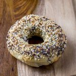 close up on an everything NY style bagel on a wooden board