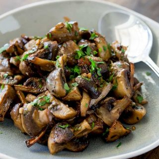 overhead view of roasted mushrooms on a grey plate