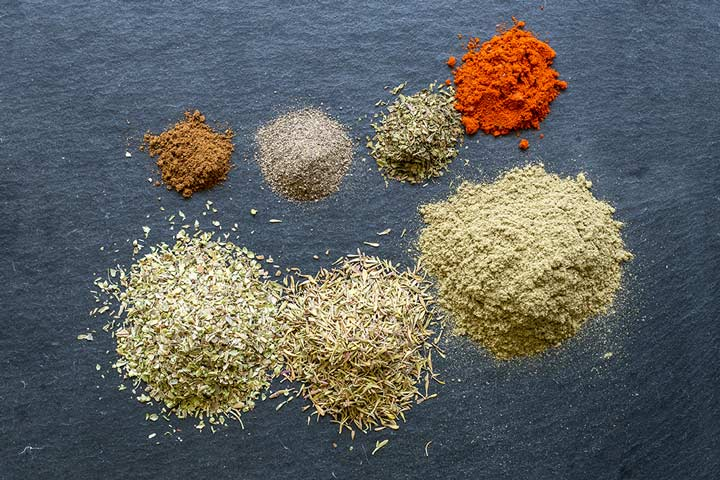 piles of herbs and spices on a slate background