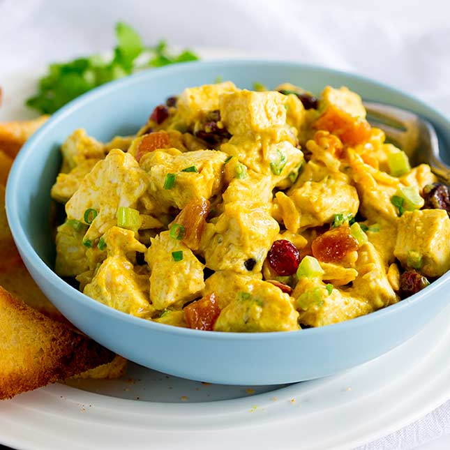 a blue bowl full of yellow curry chicken salad