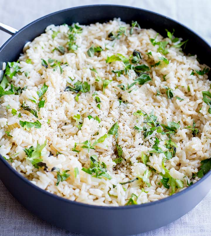 rice in a sauté pan garnished with fresh herbs