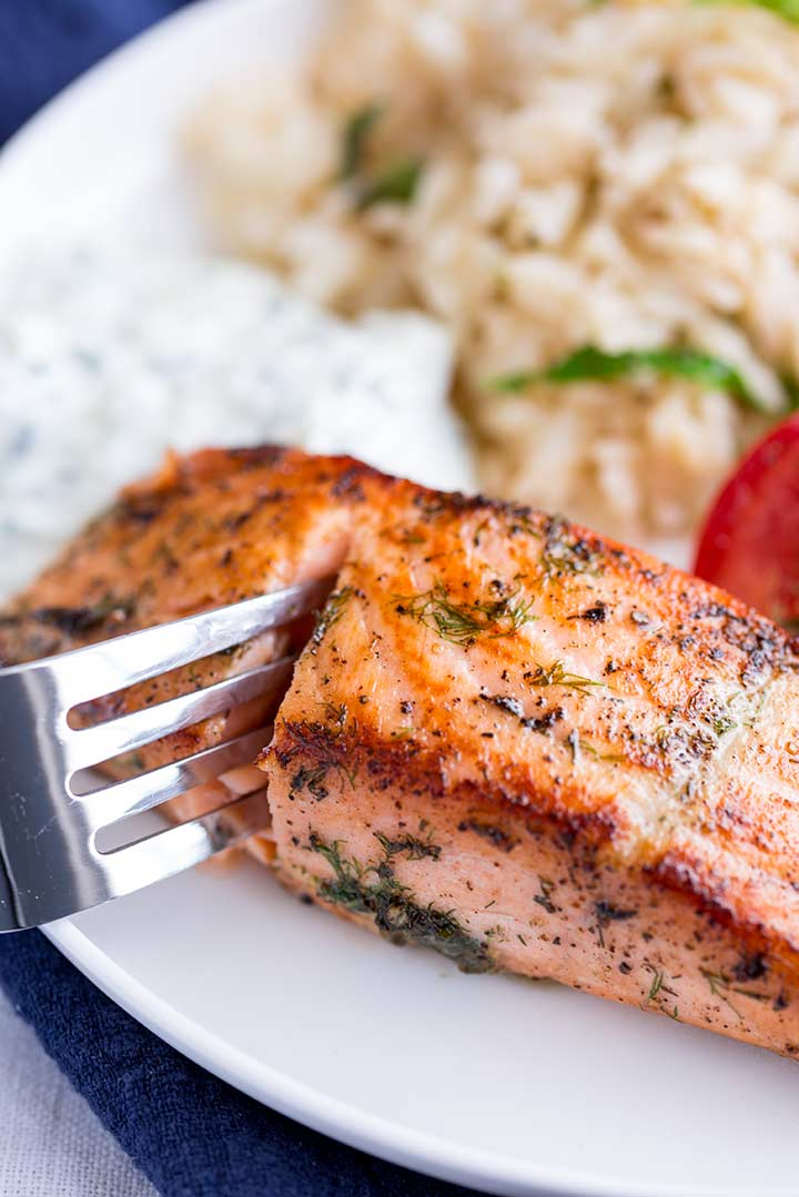 a fork cutting open a seared salmon fillet