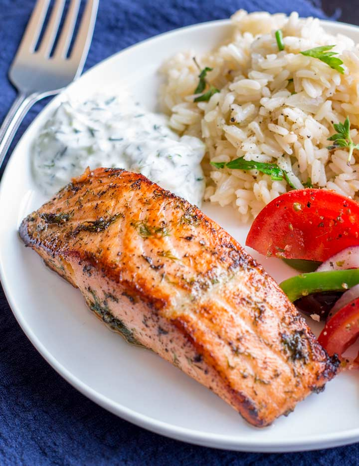 greek salmon on a white plate with rice, tzatziki and greek salad