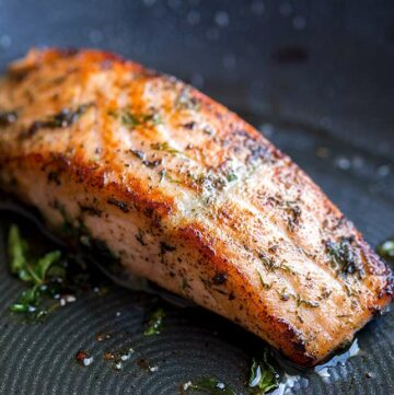 close up on the seared salmon in a black pan