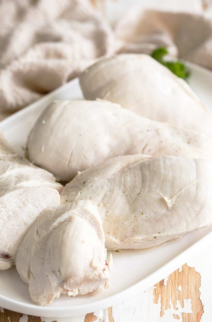 3 poached chicken breasts and one sliced poached chicken breasts on a white plate
