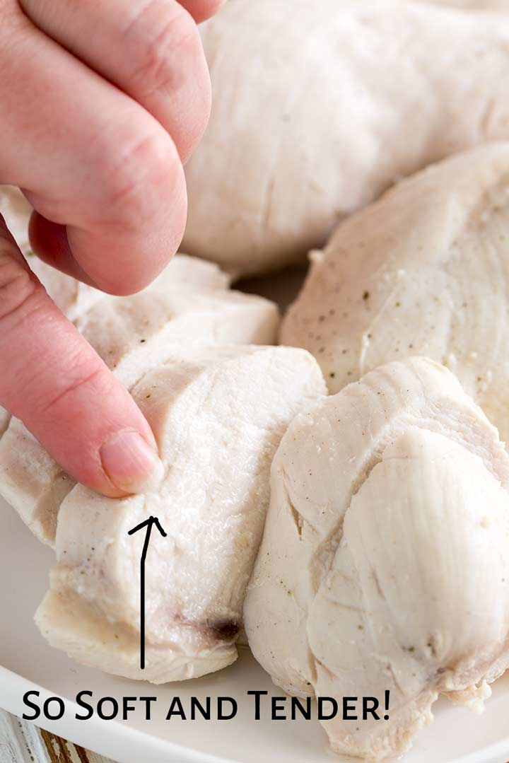 a finger pushing down on a sliced chicken breast