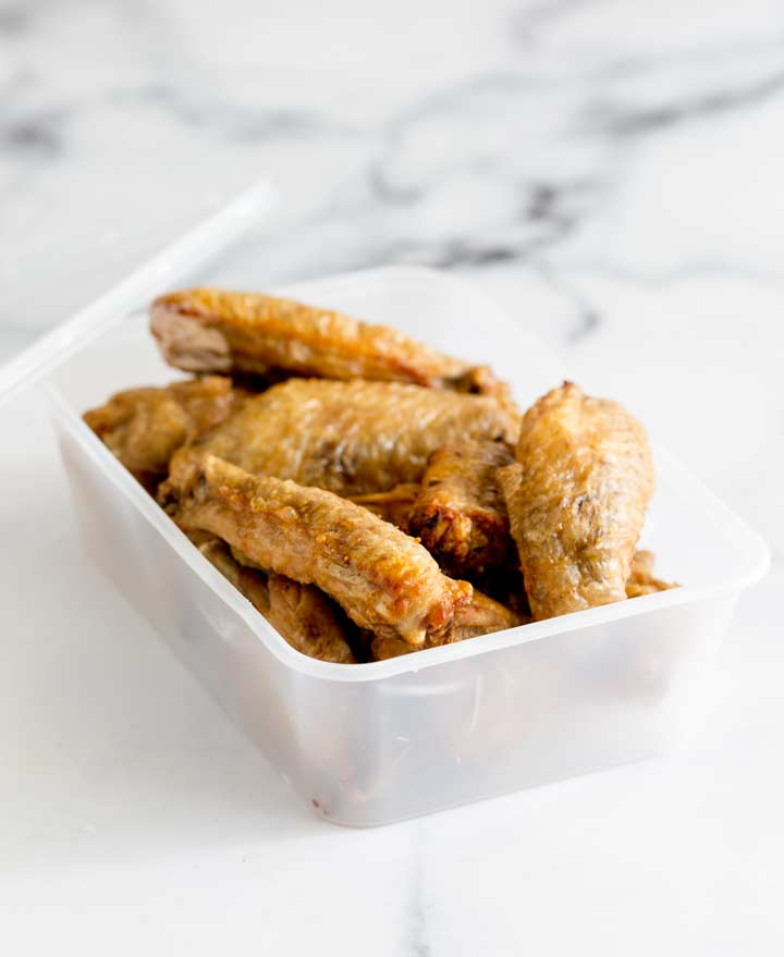 cold chicken wings in a plastic container on a marble table