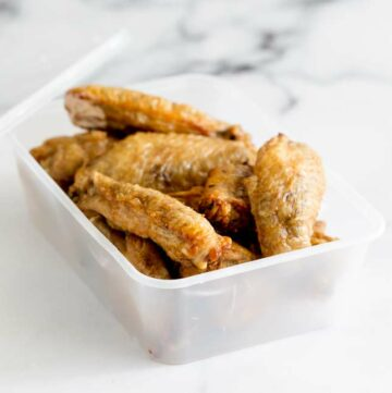 close up on the takeaway container of leftover chicken wings