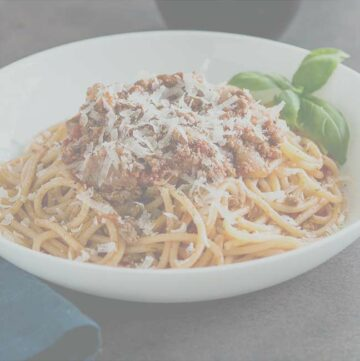 white bowl of spaghetti bolognese with a dark overlay