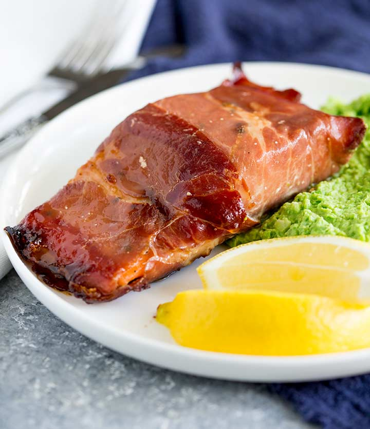 a salmon fillet wrapped in prosciutto on a white plate with lemon wedges