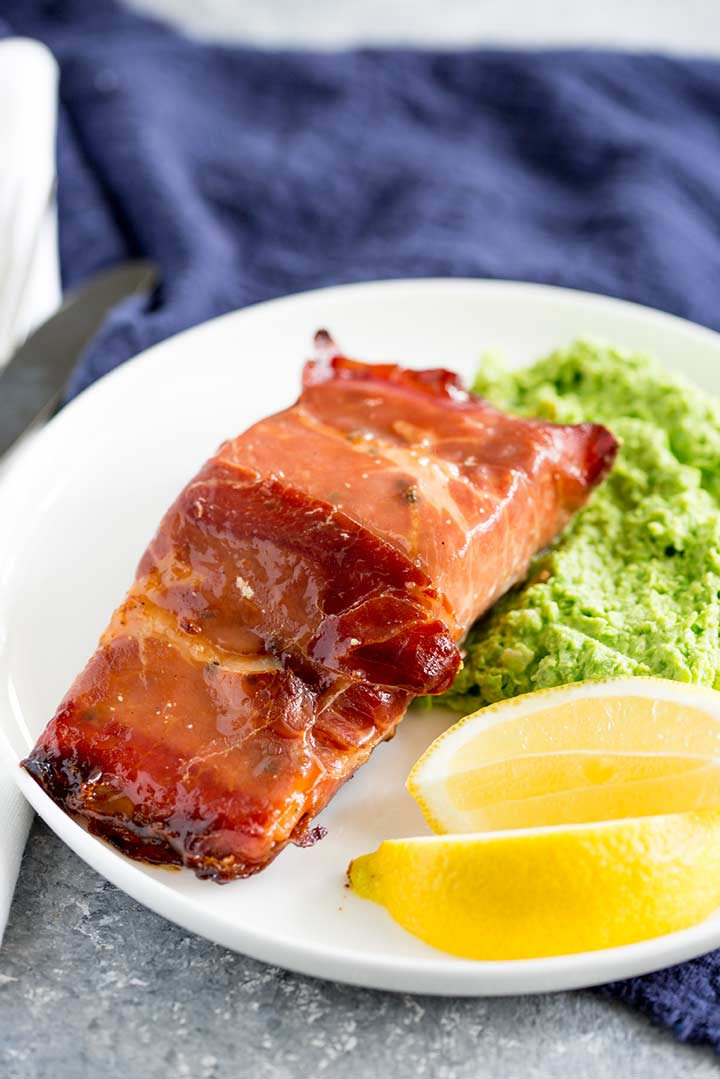 overhead view of a piece of glazed prosciutto salmon on a white plate with pea mash