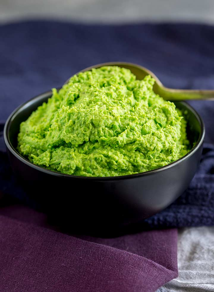a pile of green pea mash in a small black bowl
