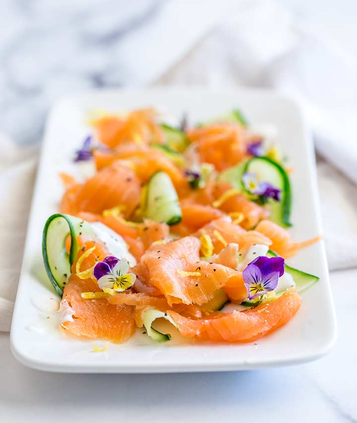 smoked salmon, cucumber ribbons and lemon zest on a platter