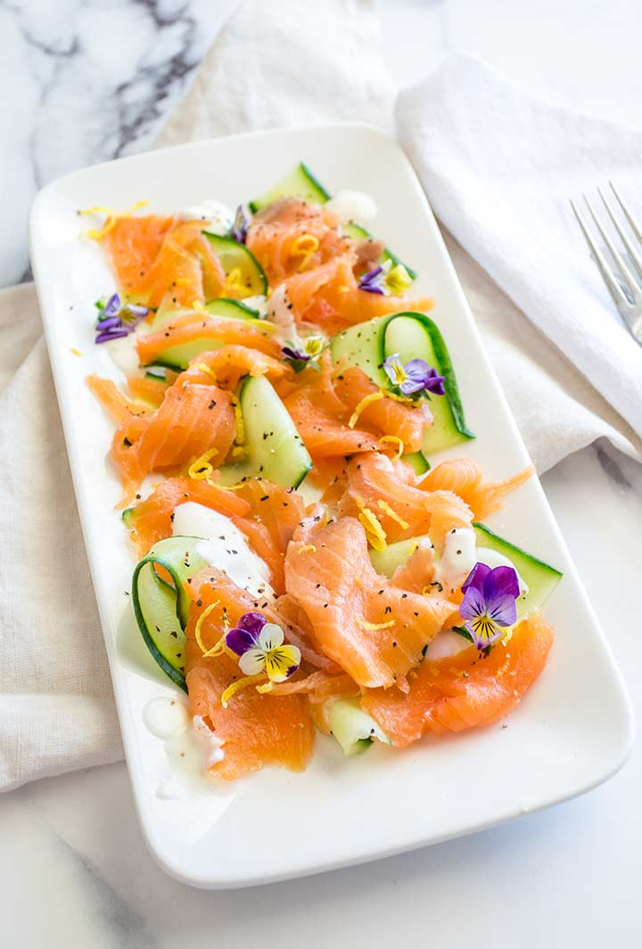 a marble table with a rectangular plate of smoked salmon and cucumber salad