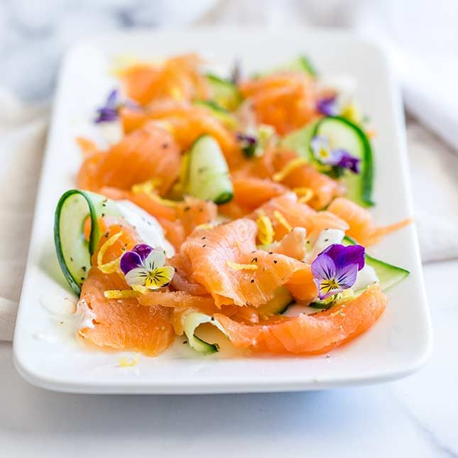 retangular platter of smoked salmon curls and cucumber ribbons on a marble countertop