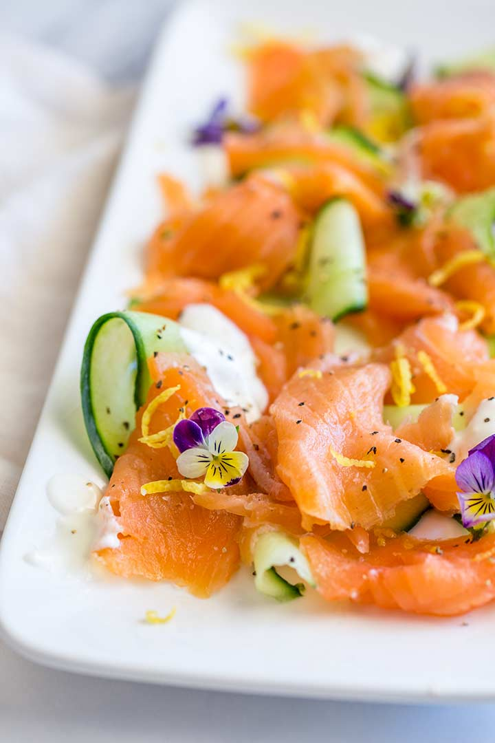 close up on a smoked salmon curls garnished with a violet flower