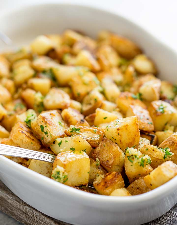 a spoon in a dish of crispy potatoes topped with garlic and parsley