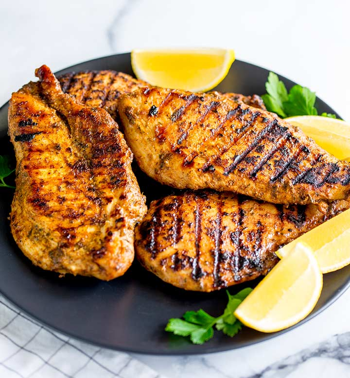 4 grilled chicken breasts on a black plate with lemon wedges