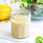 close up of a jar of hummus salad dressing on a white table