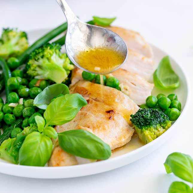 square image of a spoon of garlic butter being drizzled over chicken breasts