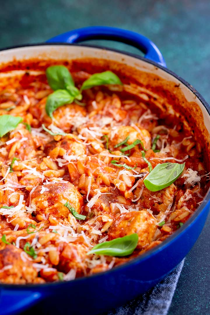 A shallow casserole with orzo and meatballs in it