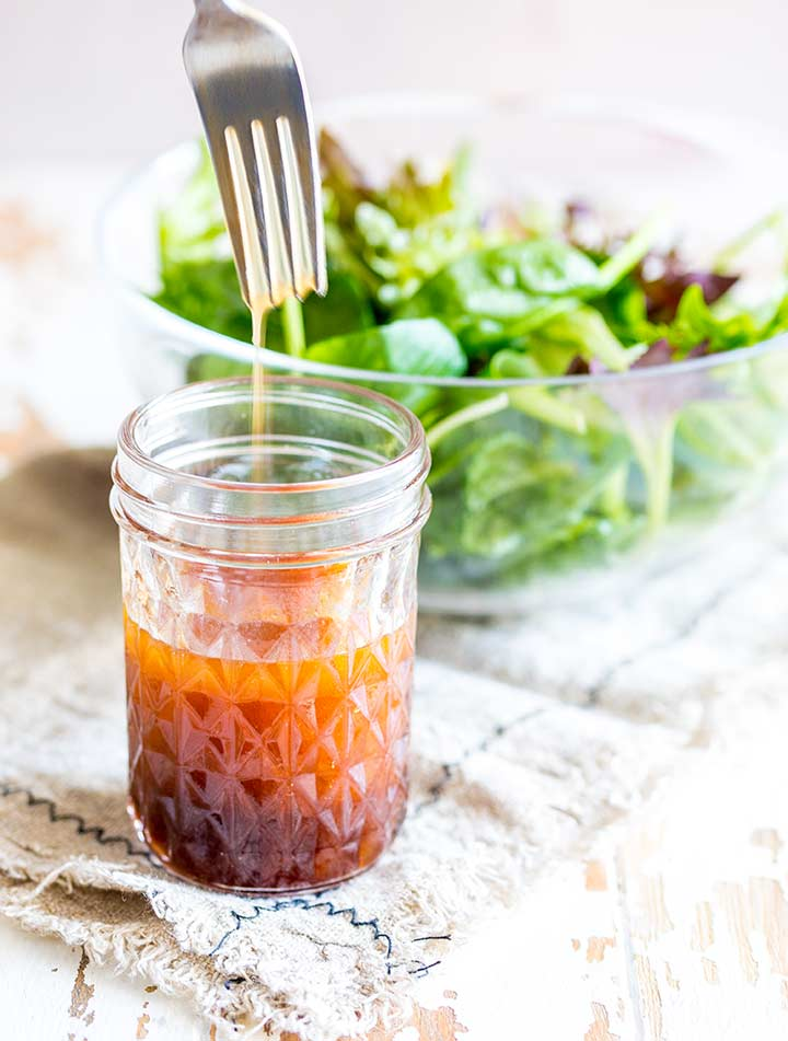 a glass jar of salad dressing with salad in the background
